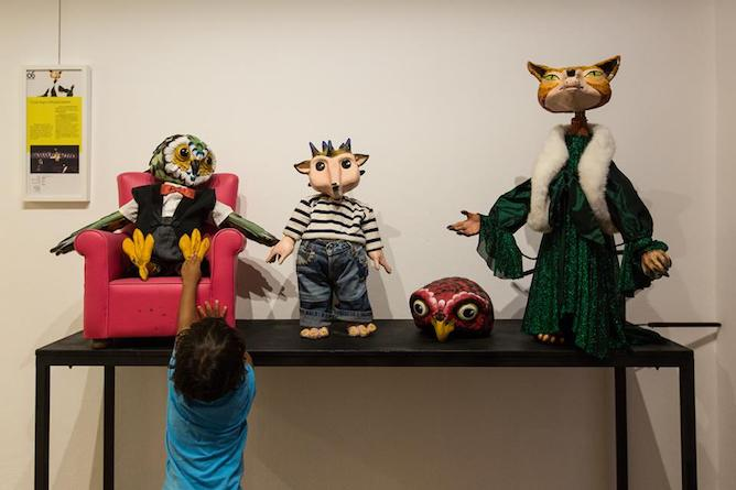 children touching real sized puppets